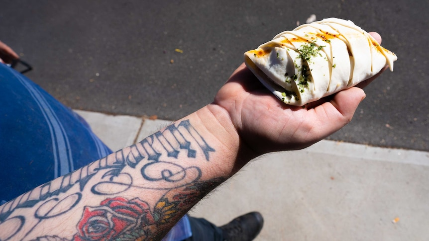 An arm lined with colourful tattoos holds out a pastry meat parcel into the sunlight.