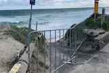 A barrier across a beach path amid stormy skies.