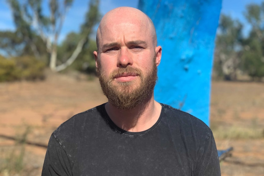Portrait of Simon Comerford in front of a blue tree.