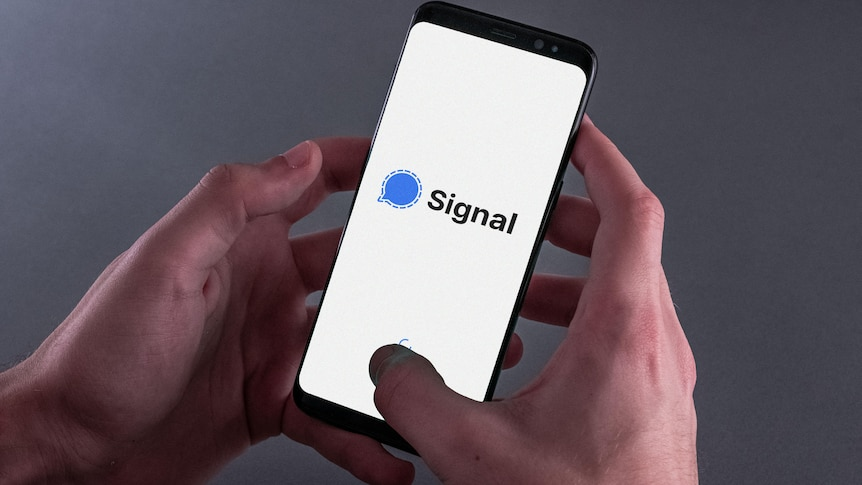 Hands hold a smartphone showing the Signal app logo