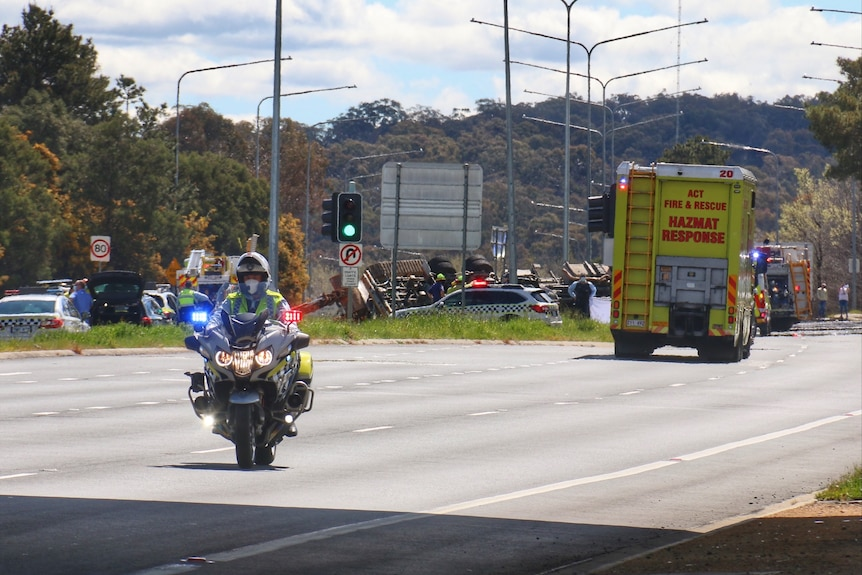 A truck can be seen lying on its roof at the scene of a fatal accident on the Barton Highway in Canberra.