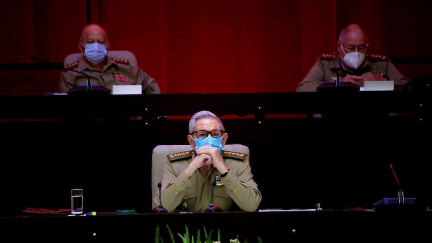raul castro sits with his hands clasped wearing a mask