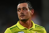 A South African male batter looks to his right as he walks off the field.