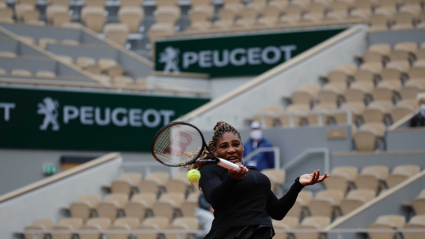 Serena Williams hits a forehand in front of empty stands at the French Open.