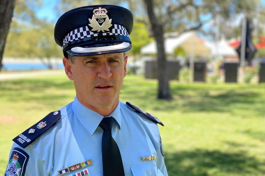Police officer in uniform speaks in a park.