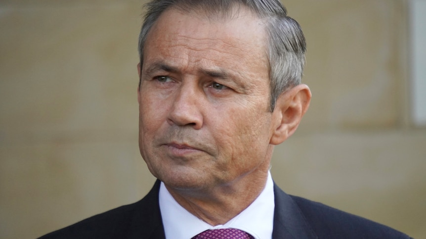 A tight head and shoulders shot of a frowning WA Health Minister Roger Cook.