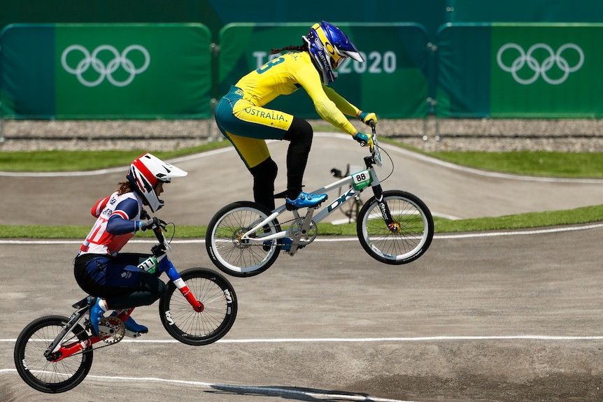 A woman wearing yellow rides a bike in the air