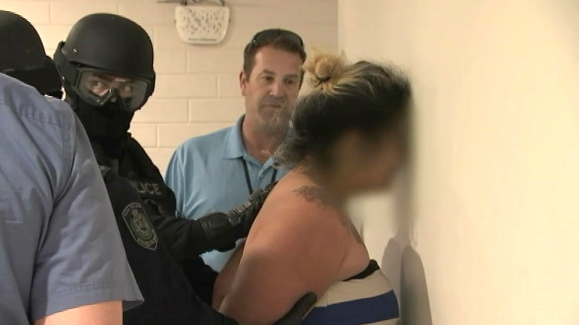 woman being held face first against a wall by police
