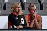 A concerned looking Super Netball coach and one of her players watch the court during a game.