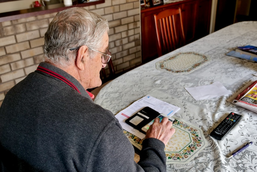 A man sitting at a table looking at a phone and telstra bills on the table.