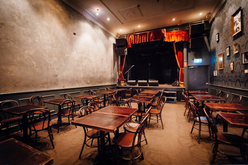 An empty room with tables and chairs in the front and a stage at the back