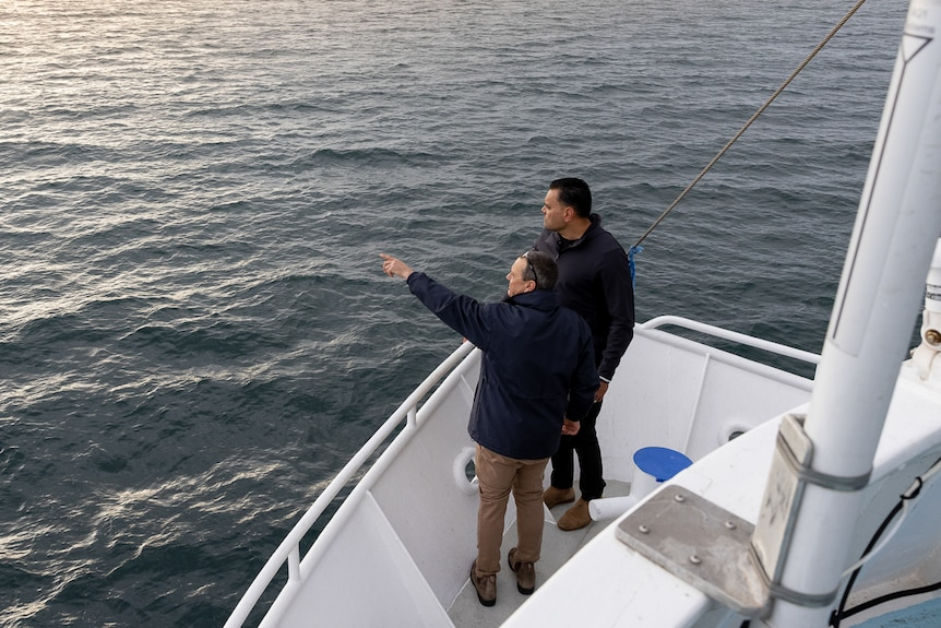 Two men stand at the front of the boat with one man pointing out to sea