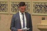 MP Fraser Ellis standing as he reads from a sheet of paper in parliament