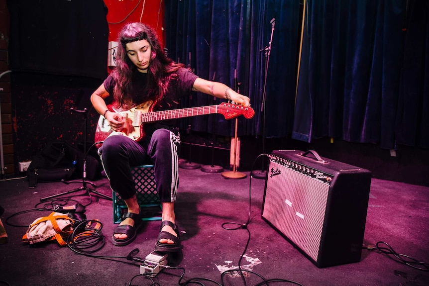 Camp Cope singer Georgie Maq tunes her guitar