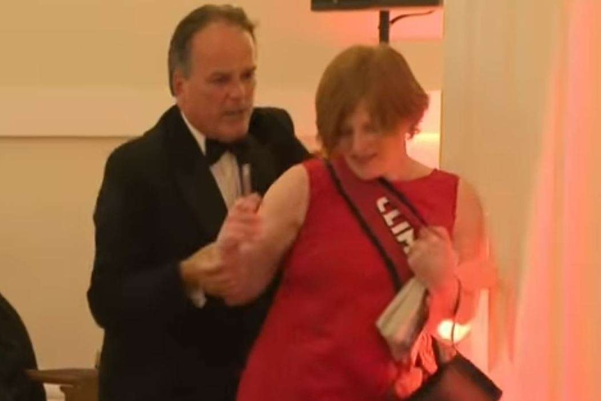 Mark Field grabs a woman in a red dress