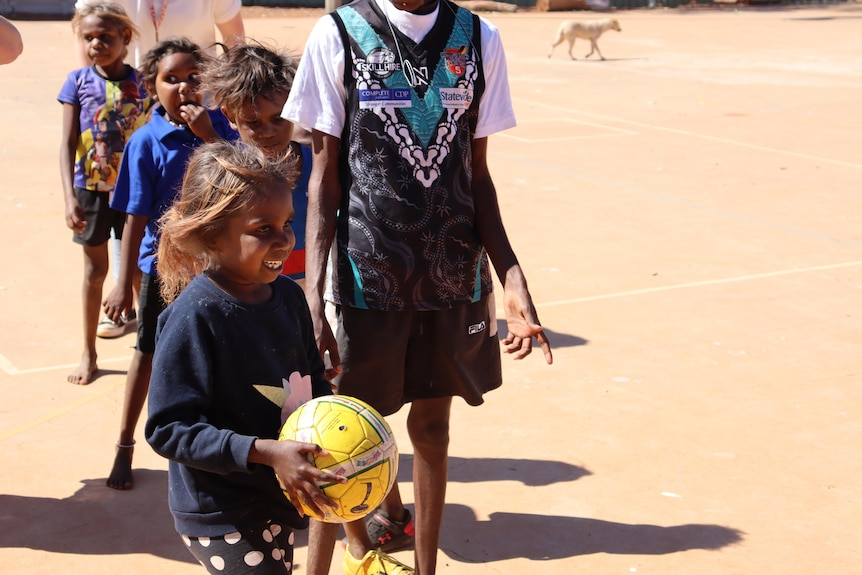 young Aboriginal girl standing at the head of a line of students, holding a yellow ball and smiling