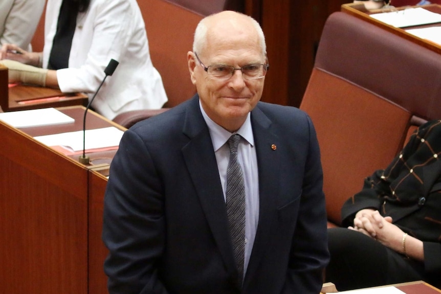 Jim Molan, with his hands crossed in front of him, smiles in the Senate. Marise Payne is sitting behind him.