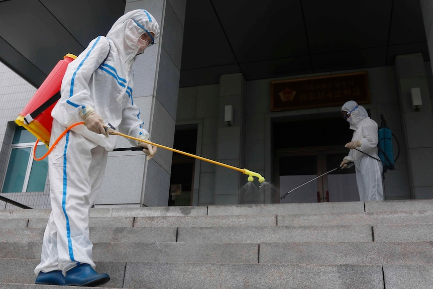 Two people in full PPE spraying disinfectant on a staircase