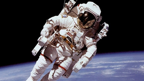 Astronaut floating in space above the Earth