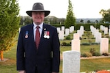 A man wearing a broad-brimmed hat and a blazer with medals, standing in graveyard.