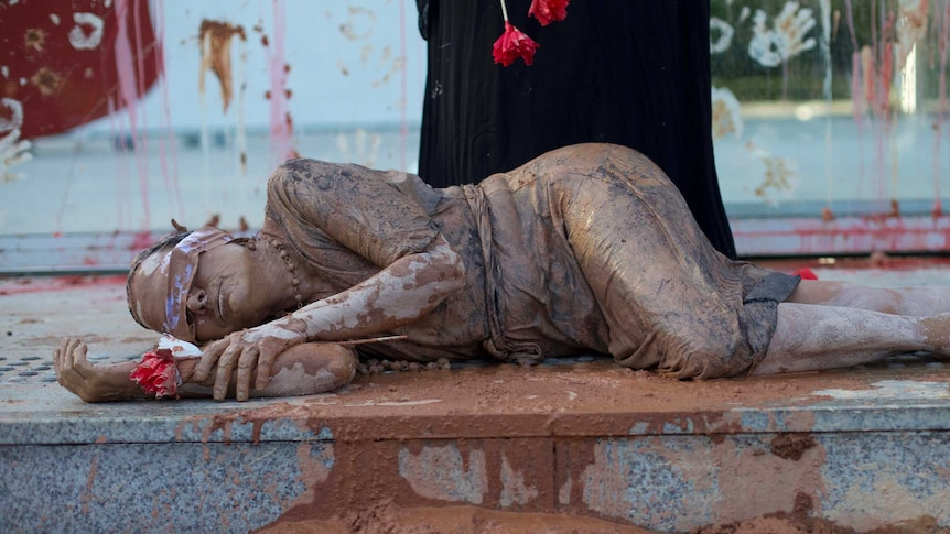 A woman covered in mud with a sash over her eyes lies in front of the granite steps of Vale SA's headquarters.
