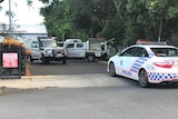 Three police cars parked behind a minibus at a school gate
