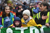Greta Thunberg comforts a crying girl has they march behind a large banner during a climate protest.