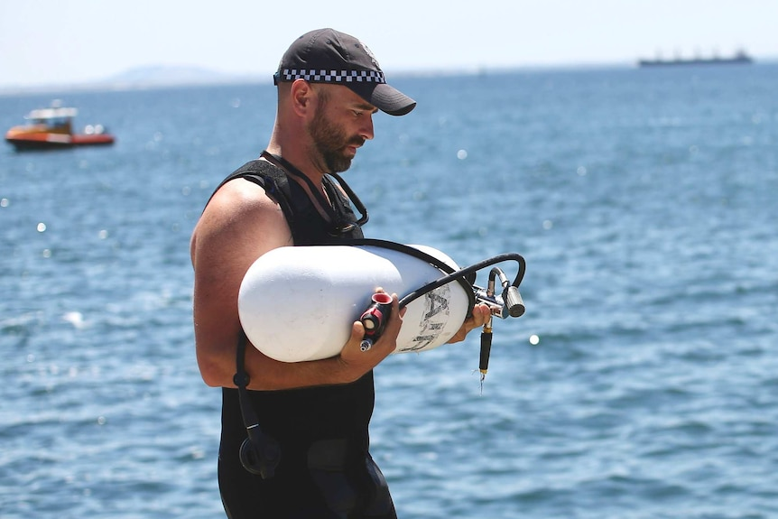 A side-on mid shot of a police diver carrying a white oxygen tank with the ocean in the background.