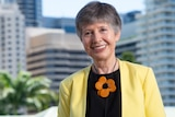 An image of Professor Lidia Morawska smiling wearing a yellow jacket, black blouse and orange flower necklace  buildings, tree