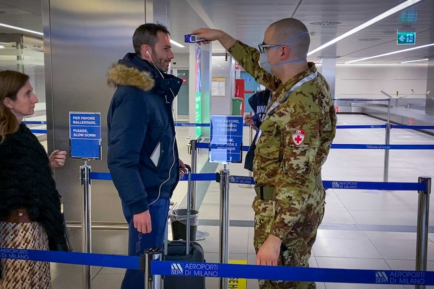 A man in military fatigues takes the temperature of an airline passenger in an airport.