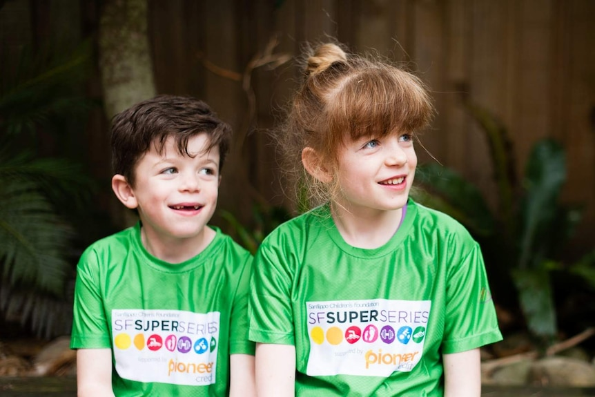 A young brother and sister sit alongside each other in green matching shirts.