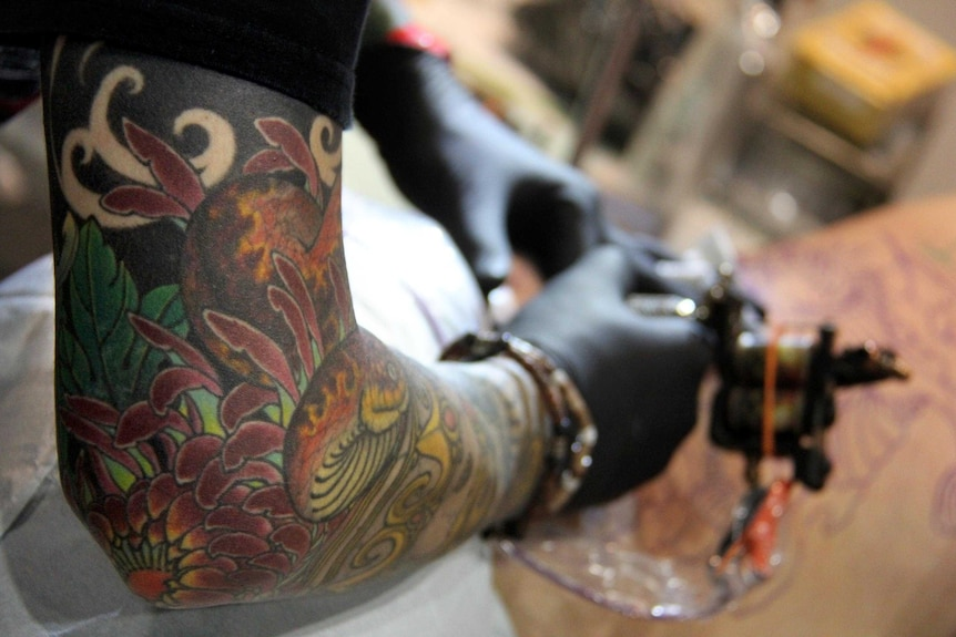 A tattooist works on a client.