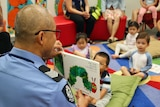 Police officer reads book to children