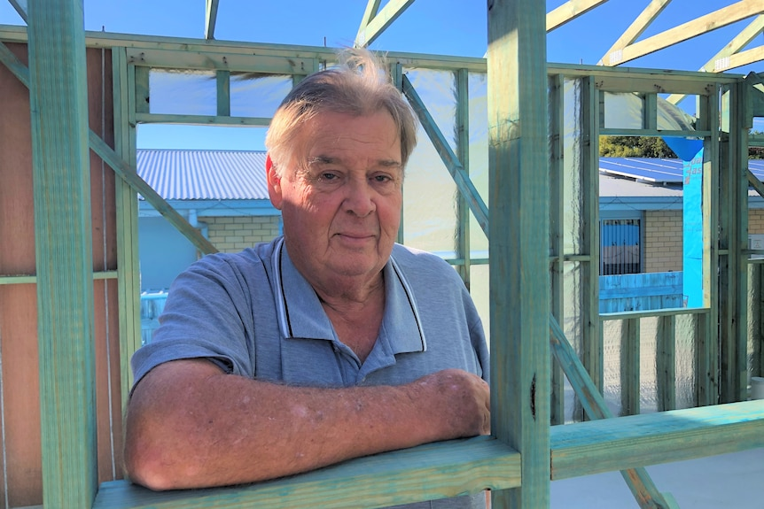 Man leans through a gap in a in timber house frame