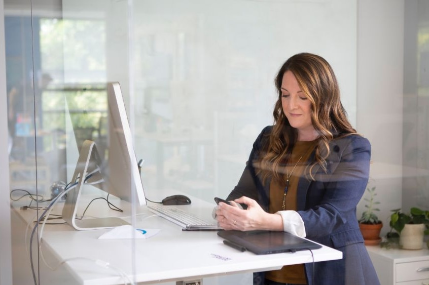A woman at a standing desk in an office