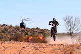 A motorcyclist soars through the air over a sand dune, with a helicopter behind him.