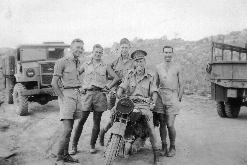soldiers pose on a motorbike