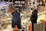 Two shoppers in masks wait at the counter of a deli at South Melbourne Market