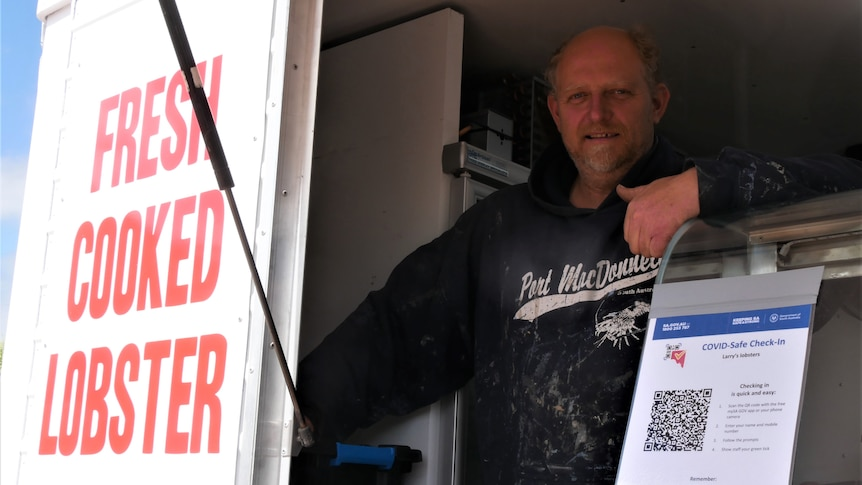 A middle aged man smiles with his thumb up from the window of a food truck. Wearing a paint splattered Port Macdonnell hoodie