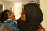 Shizleen Aishath holding her 2-year-old son Kayban Jamshad in her arms.