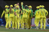 The entire Australian team meet in a group as they celebrate a New Zealand wicket.