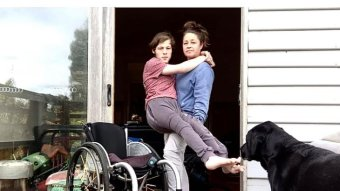 Woman holds teenage boy in arms, wheelchair in foreground