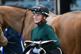 Female jockey standing in front of her horse