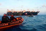 You look at coast guard personnel on small rubber boats approaching a cluster of large fishing ships.