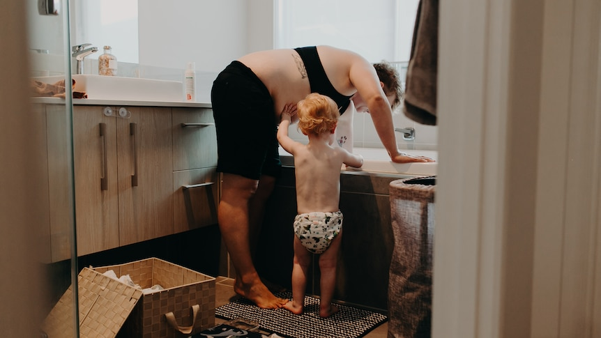 A mother is bent of as she runs a bath while her toddler stands with her.
