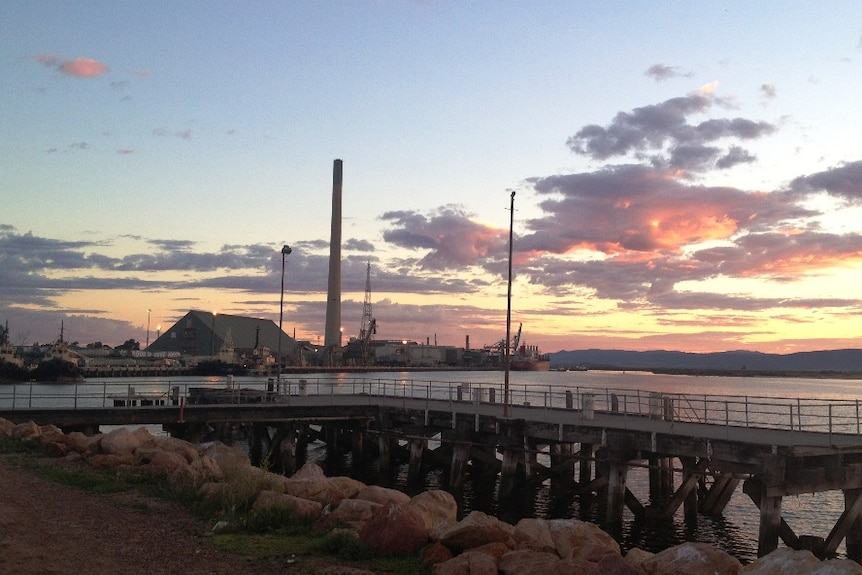 The tall chimney of a large smelter on the water's edge projects into the sky as the sun sets behind it