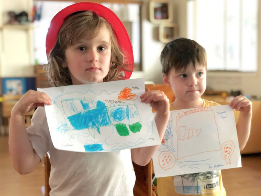 Two kindergarten-aged boys hold drawings of fire trucks.