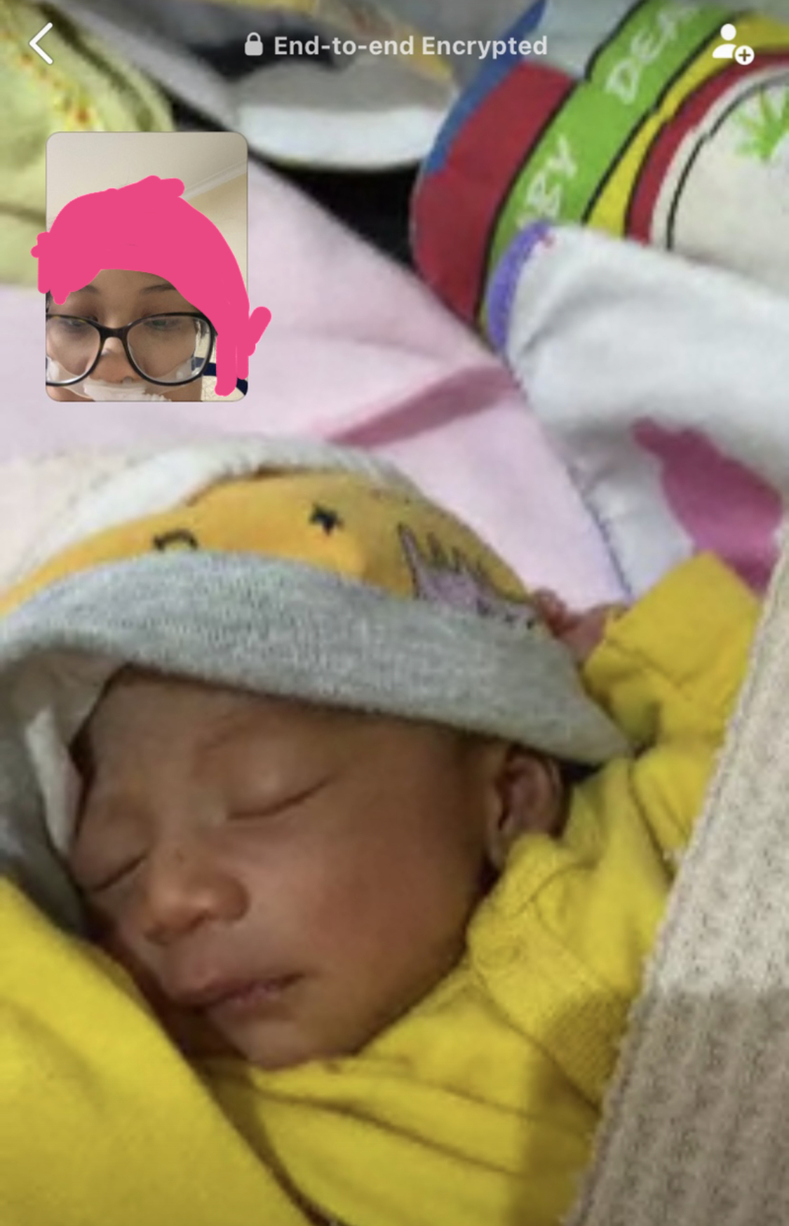 A woman appears on videocall with her newborn baby.