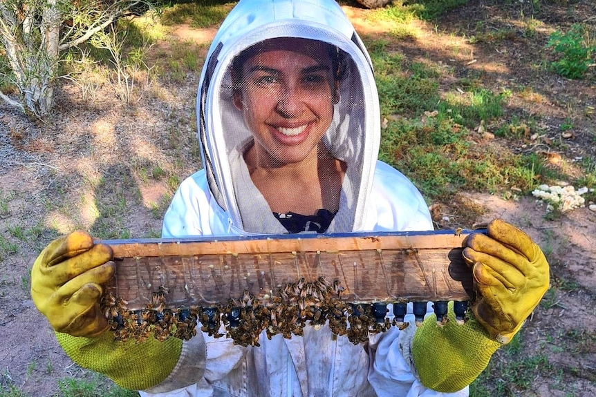 An indigenous woman in a bee suit holding a beehive cell