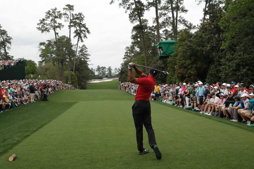 An image taken behind a male golfer as he tees off on the 18th hole at the Masters while watched by a gallery of spectators.